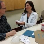 Meghan Bolinger demonstrates inhaler use for a patient.