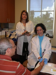 """Shara Elrod, Pharm.D. (standing left) and Elizabeth Sherman, Pharm.D  (seated right), administer a rapid HIV test to a patient."